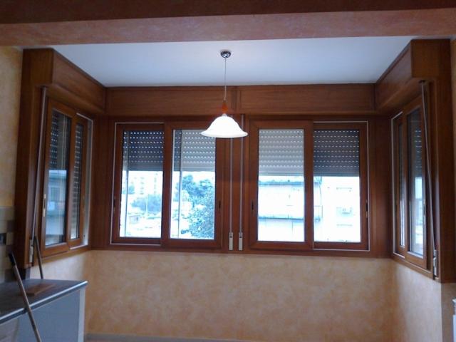 Veranda in misto legno alluminio costituita da scorrevoli con cassonetti in legno e tapparelle in alluminio